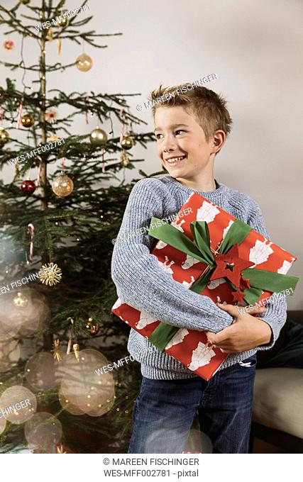 Boy holding a large Christmas present in front of tree