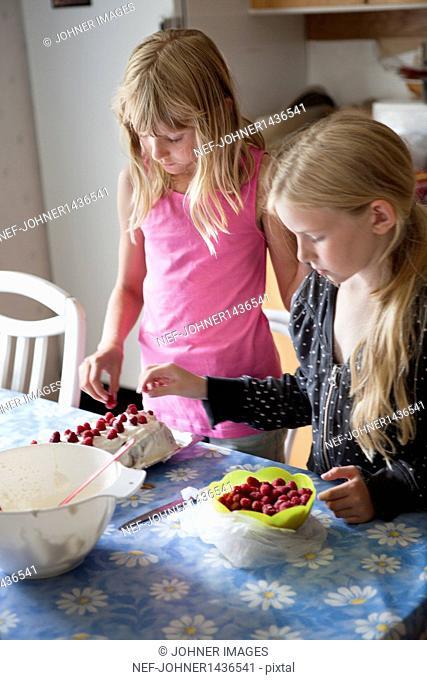 Two girls preparing cake in kitchen