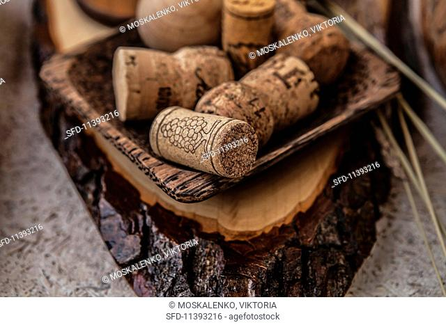 Wine and champagne corks in a wooden bowl on a piece of wood