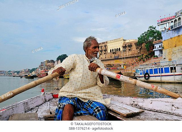 Man rowing boat for short sightseeing by the ghat at Ganges river