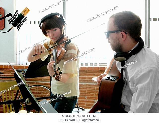 Young man and woman playing violin and guitar in music room rehearsal
