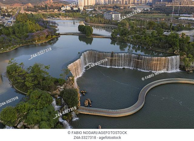 Aerial 360 degree view of the Kunming Waterfall Park at sunset, one of the largest manamde waterfalls in the world