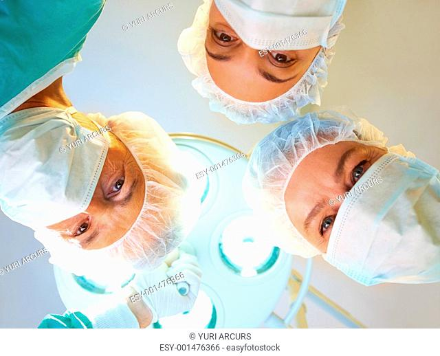 Medical concept - Confident surgeons during an operation looking down at the patient