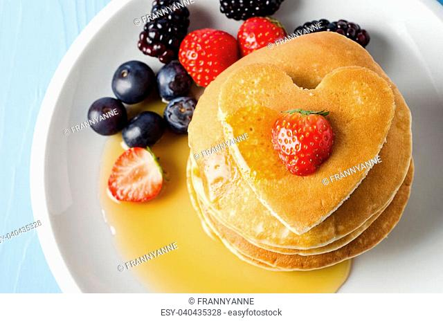 Overhead shot of a stack of pancakes on a white china plate with Summer fruits, topped with a heart shaped one and a strawberry