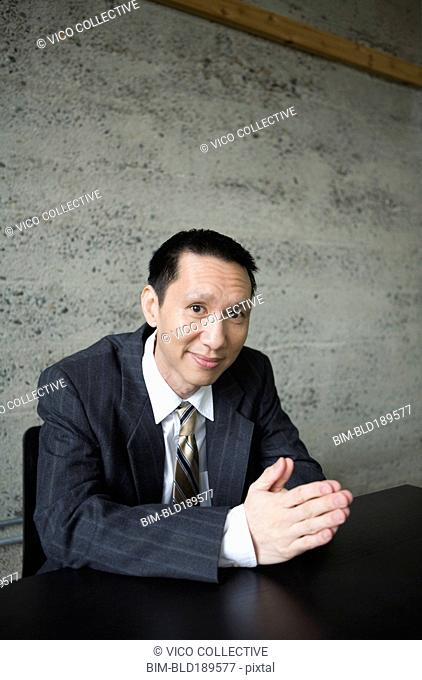 Pacific Islander businessman sitting at table