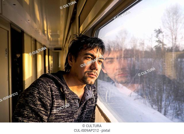 Portrait of mid adult man gazing out of train window