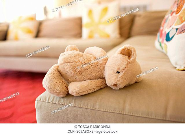 Teddy bear lying on couch