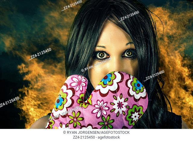 Cooking concept of a woman expressing shock horror with cooking glove to face on kitchen fire background. Bad cook