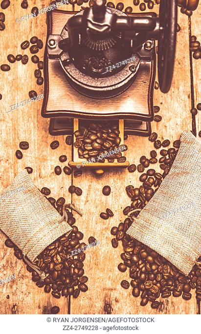 Top view of old vintage grinder with coffee beans in textile bags on wooden table