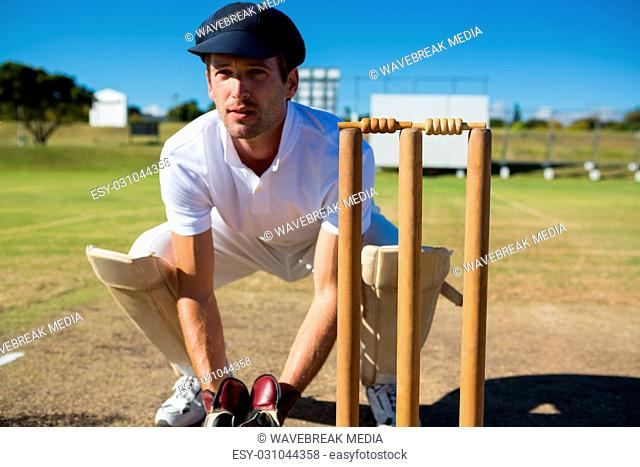 Wicket keeper crouching by stumps during match