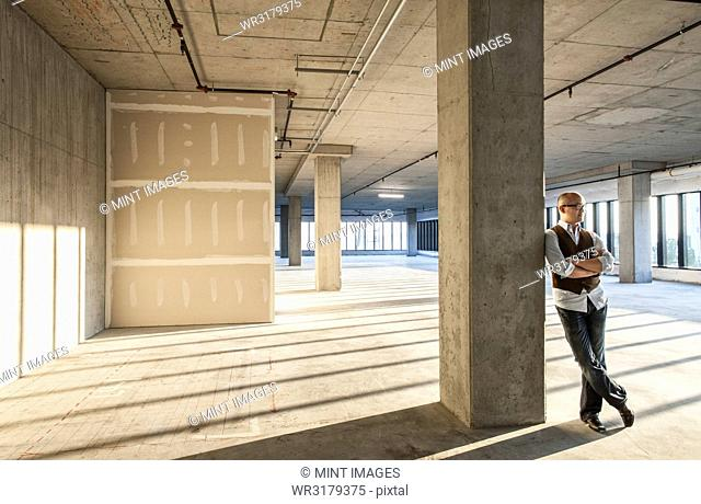 Asian businessman standing in a large empty raw office space