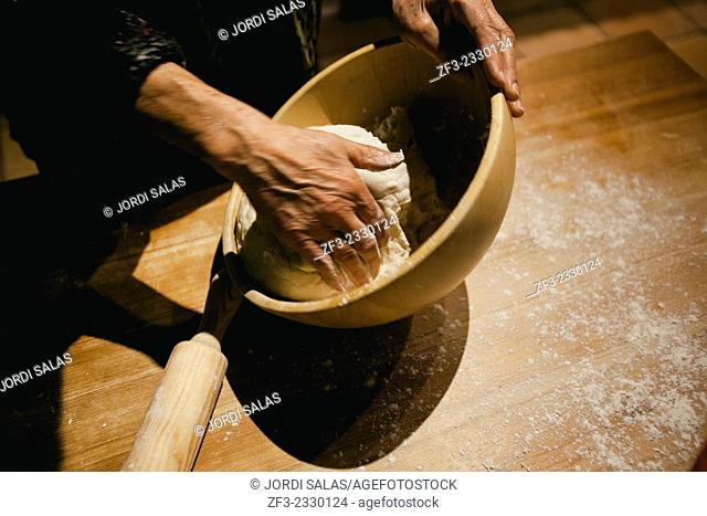 Hands kneading wheat bread dough on a wooden table