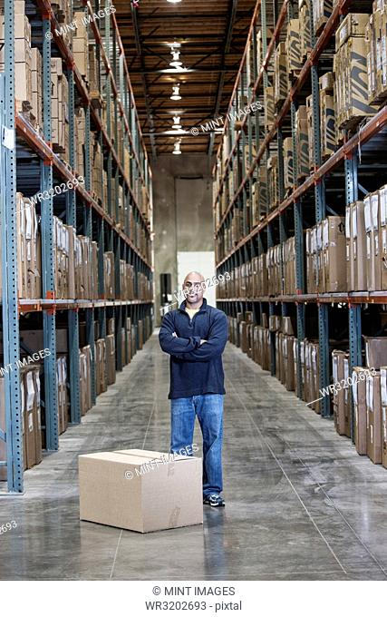 A black warehouse worker standing near boxed products in a distribution warehouse