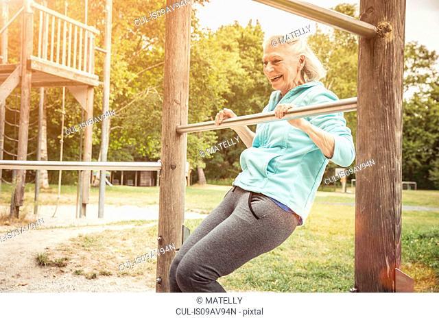 Senior woman in park doing limbo under metal bar smiling