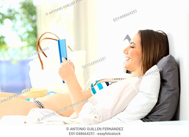 Side view portrait of a happy hotel guest reading a book lying on a bed in an hotel room during a travel on summer vacations