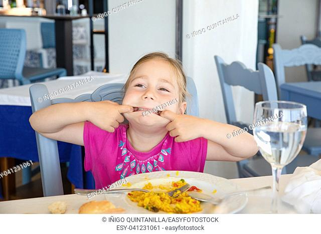 portrait of four years old blonde girl making grimaces stretching her mouth, sitting in restaurant eating Spanish paella rice