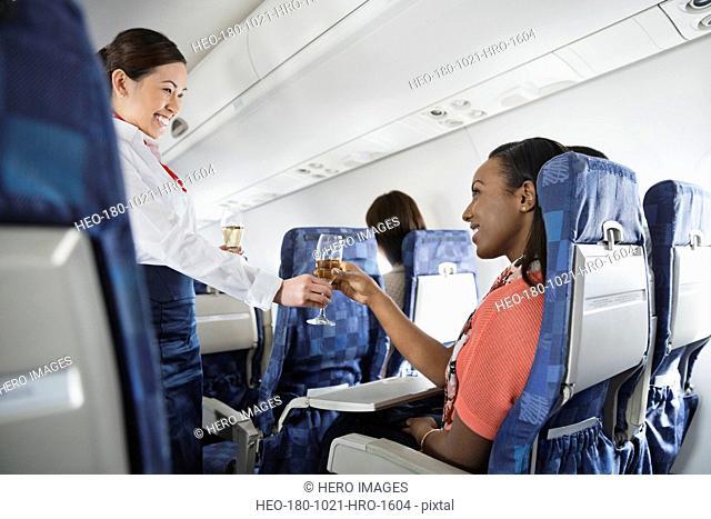 Flight attendant serving champagne to passenger