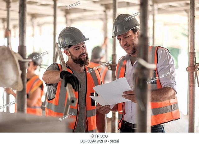 Male builders looking at blueprint on construction site