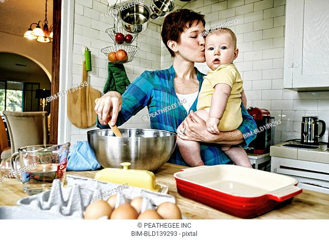 Caucasian mother kissing baby and cooking in kitchen