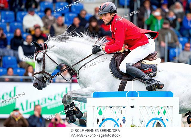 German rider Denis Nielsen on his horse 'Cashmoaker' jumps a hurdle at the CHIOinAachen,Germany, 30 May 2015. He ranked third in the show jumping competition