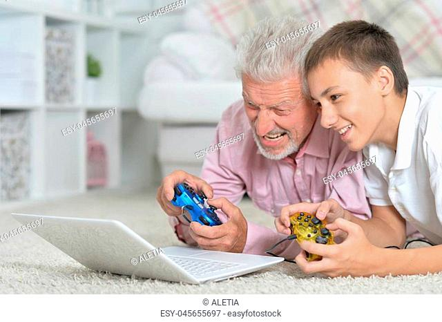grandfather and grandson lying on floor and playing computer games on laptop