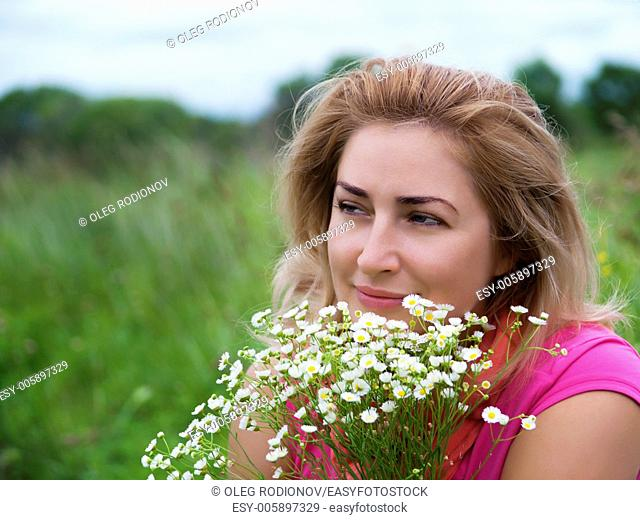 Portrait of young woman with bouquet of daisies
