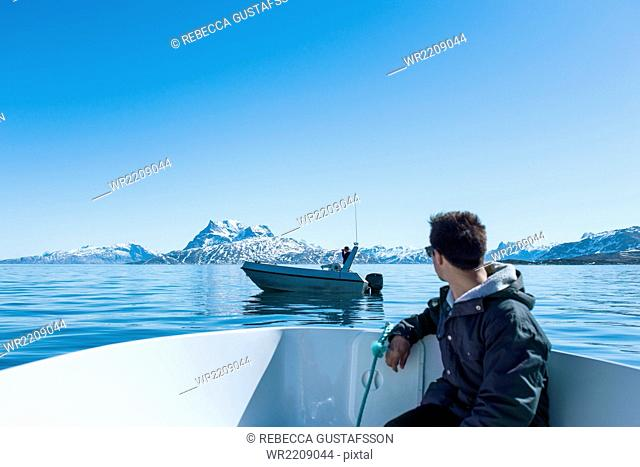 Young man sitting in boat looking at snowcapped mountains