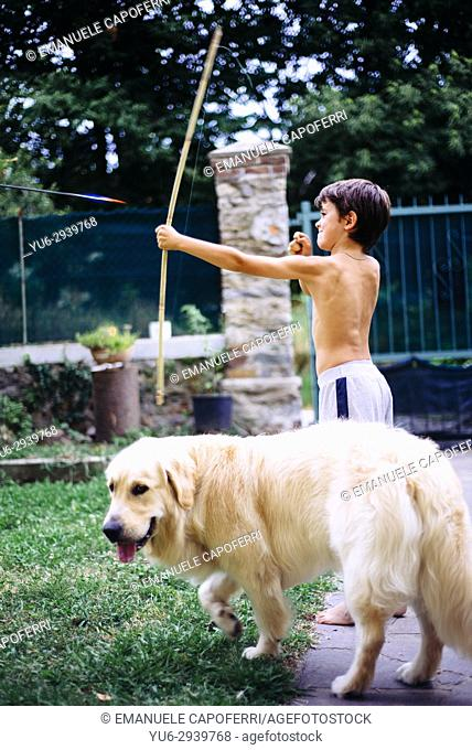 Boy plays with the dog and a bow in the garden