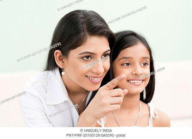 Woman pointing away and smiling with her daughter