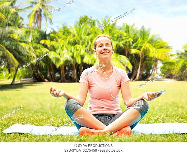 woman with smartphone and hones meditating at park
