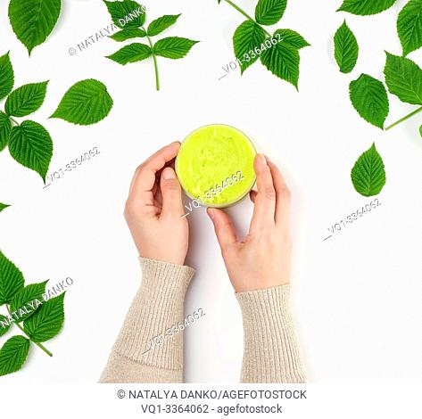two female hands of a young girl with smooth skin and round jar with cream, white background with green leaves of raspberry