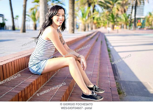 Spain, Barcelona, portrait of smiling young woman with nose piercing and tattoos sitting on steps at sunlight