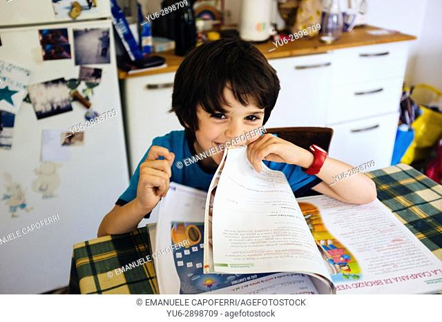 Boy doing homework. Italy