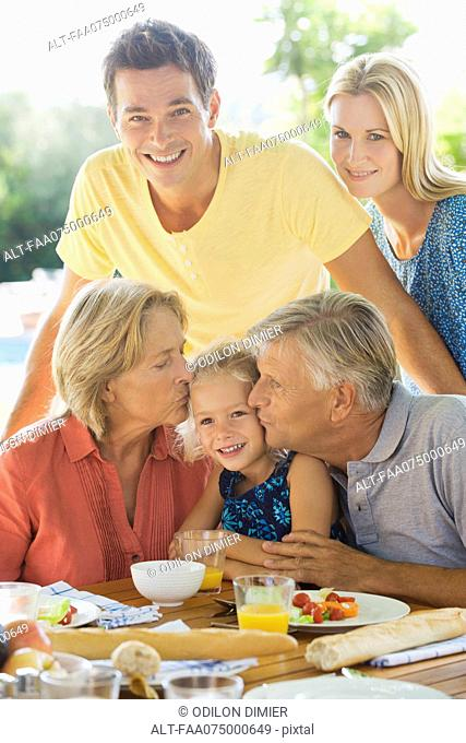 Family having breakfast outdoors, grandparents kissing granddaughter's cheeks, portrait