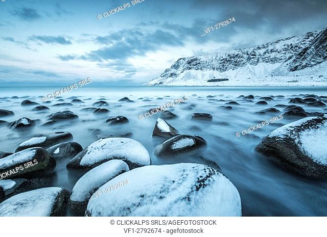 Rocks in the cold sea and snow capped mountains under the blue light of dusk Unstad Lofoten Islands Northern Norway Europe