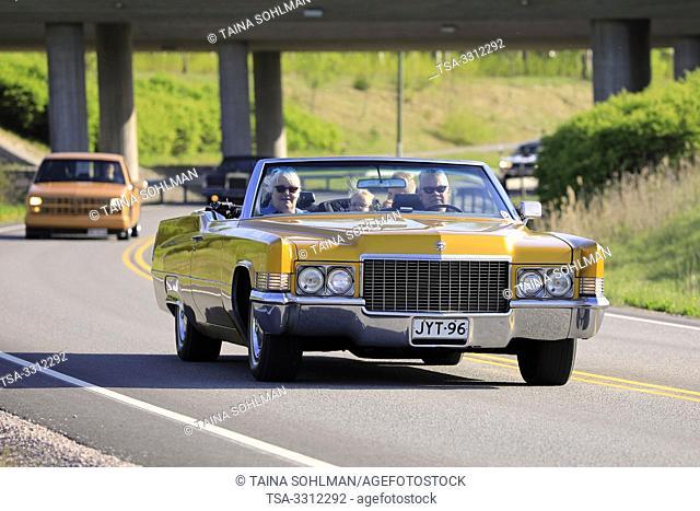 Salo, Finland. May 18, 2019. People cruising on classic yellow 1970s Cadillac convertible along highway on Salon Maisema Cruising 2019