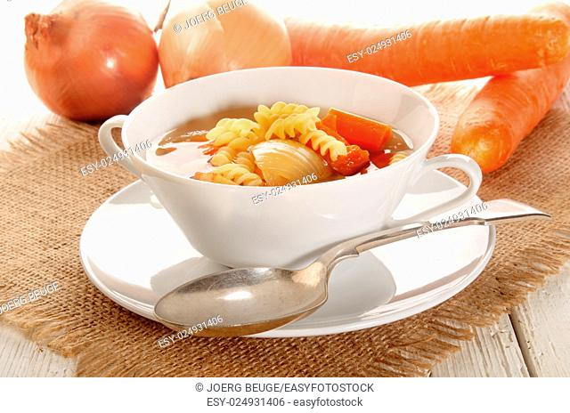 vegetable soup with carrots, onions and noodles and spoon