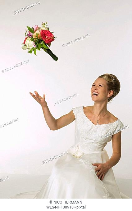 Young bride tossing bridal bouquet, laughing
