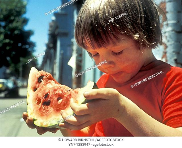 young boy enjoying a huge slice of watermelon