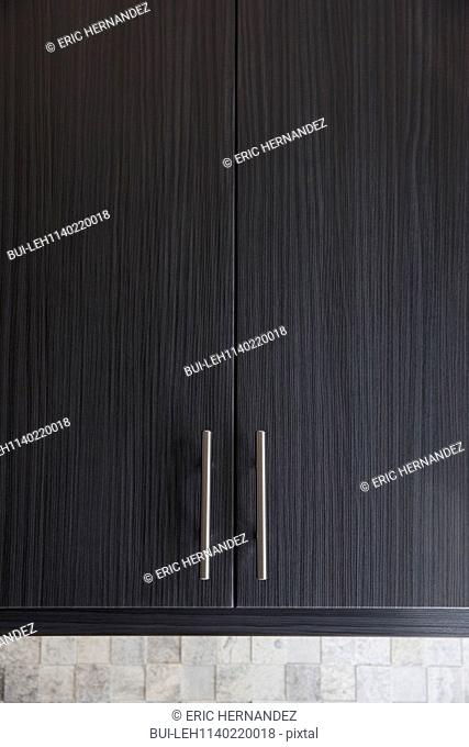 Detail shot of black cabinet with handles