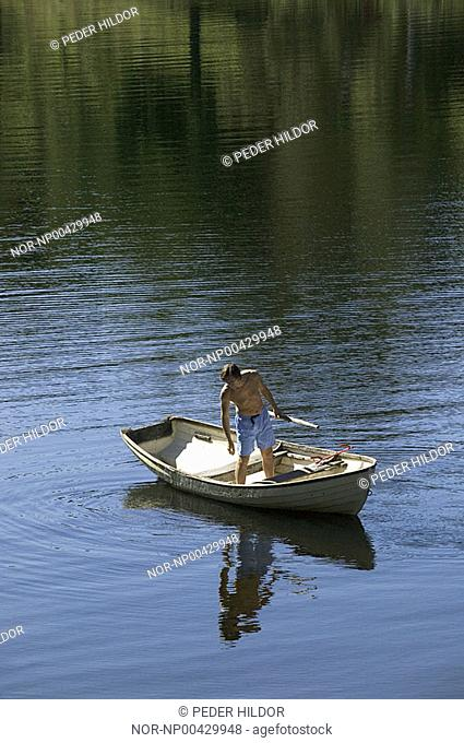 A man standing on the boat and looking at his reflection in the river