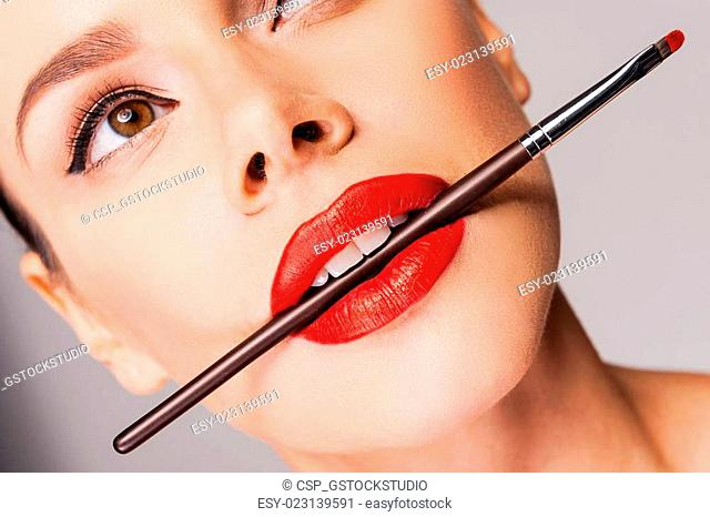 Cosmetics artistry. Close-up of a beautiful woman with red lips holding make-u[p brush in her mouth and looking away while standing against grey background