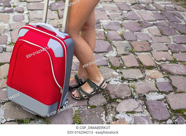 Travel to Europe, red suitcase near beautiful female legs on the pavement