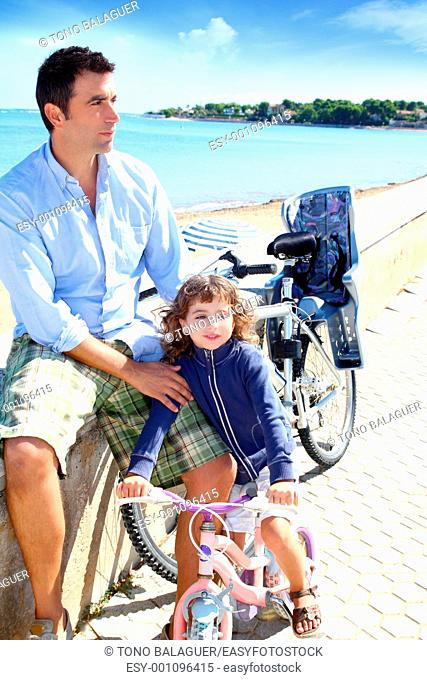 daughter and father on bicycle in beach sea vacation outdoor