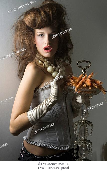 Portrait of sexy woman in corset holding plateful of prawns