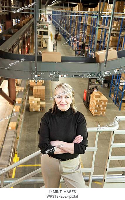 Overhead view portrait of a female Caucasian executive in a sweater and slacks surrounded by large racks, conveyor belts