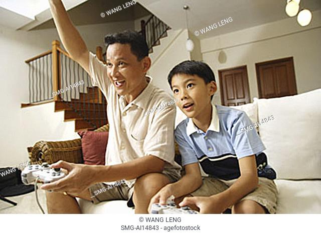 Father and son, sitting on sofa, holding video game controllers, father with arm raised
