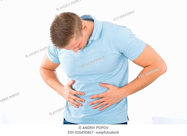 Young Man Suffering From Stomach Ache Standing At Home