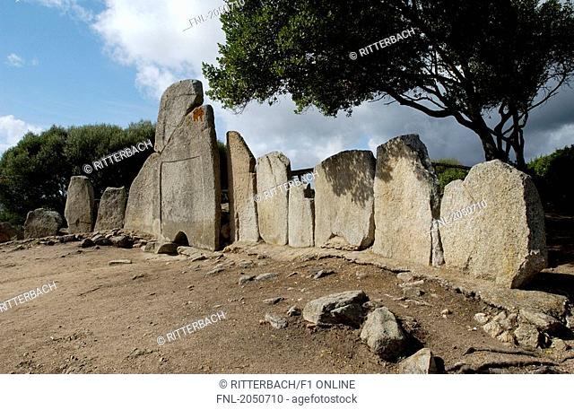 Old ruins of stone tomb under cloudy sky, Coddu Vecchiu Giant's Tomb, Arzachena, Sardinia, Italy