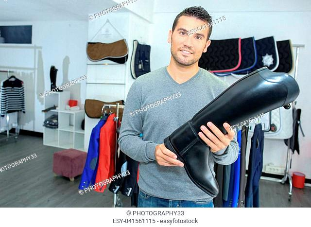 Man in equestrian store holding riding boot